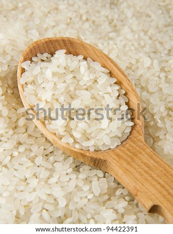 uncooked rice in wooden spoon on seed