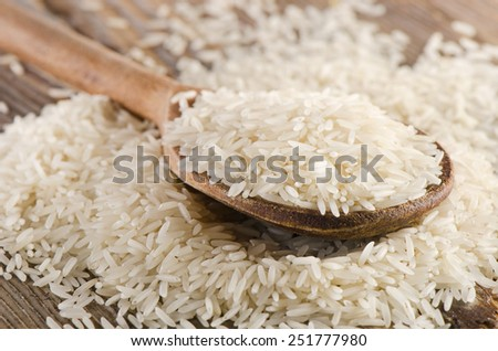 Uncooked rice in wooden  spoon . Selective focus - stock photo