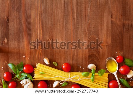 Uncooked spaghetti, cherry tomato, basil, garlic and olive oil, ingredients for cooking pasta, food background - stock photo