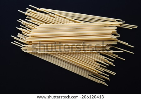 uncooked spaghetti on a black surface