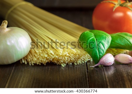 Uncooked spaghetti on dark wooden background with tomato, basil, onion and garlic. Preparation for cooking spaghetti - stock photo