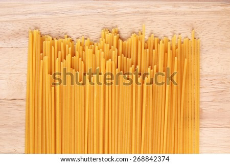 Uncooked spaghetti on wooden background - stock photo