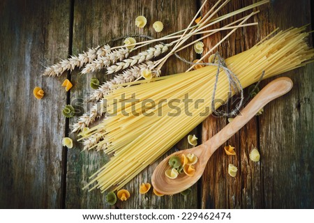 uncooked spaghetti, wheat ears and a wooden spoon on a wooden background. italian food ingredients - stock photo