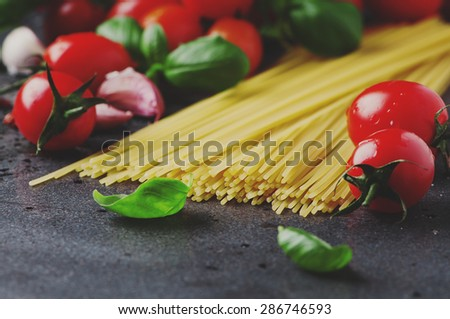 Uncooked spaghetti with tomato and basil, selective focus and toned image