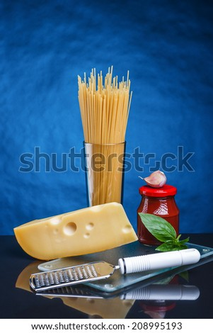 uncooked spaghetti  with tomato paste, cheese and basilic