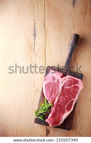 Uncooked tender porterhouse or t-bone steak on an old wooden board with a sprig of fresh rosemary waiting to be cooked, view from above on wood with copyspace - stock photo