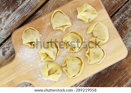 Uncooked tortellini laid out on wooden board  - stock photo