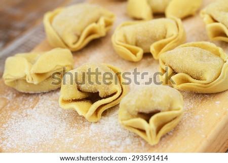 Uncooked tortellini on wooden board  - stock photo