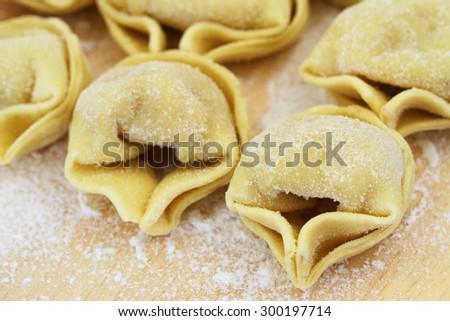 Uncooked tortellini on wooden board, closeup  - stock photo