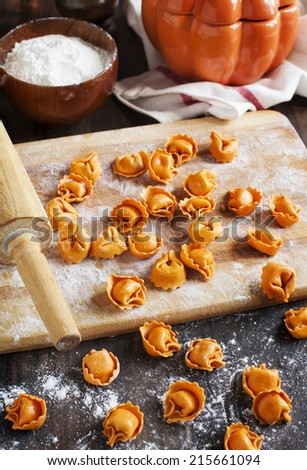 Uncooked tortellini with cheese on a table - stock photo