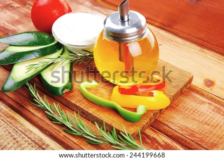 uncooked vegetables with olive oil over wooden table - stock photo