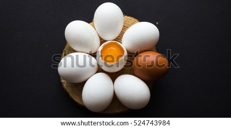 uncooked white eggs in a tree in a circle. in the middle of the egg open. black background