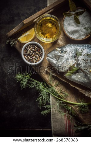 Uncooked whole fresh fish with herbs, olive oil and spices for marinating and rubbing lying on a vintage wooden tray in a rustic country kitchen, overhead view with copyspace - stock photo