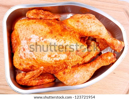 Uncooked whole marinated chicken in aluminum foil tray - stock photo