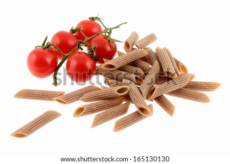 Uncooked whole wheat pasta with tomato isolated on a white background - stock photo
