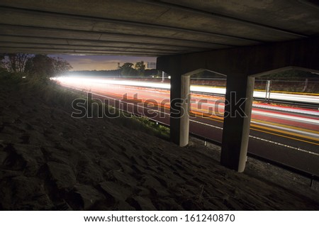 under a motorway bridge with light trails on M6 - stock photo
