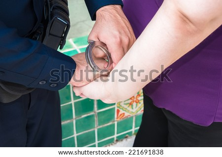 Under Arrest : Law enforcement officer handcuffing woman. Detail. Close up. - stock photo