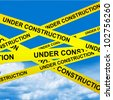 Under Construction Caution Tape With  Blue Sky Background - stock photo
