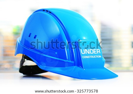 Under construction concept. Blue helmet on white table. - stock photo