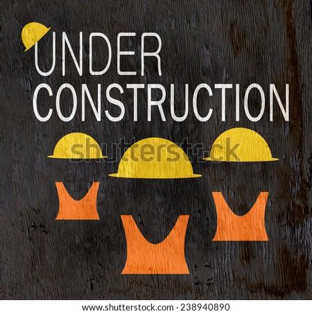 under construction graphic design on wood grain texture - stock photo