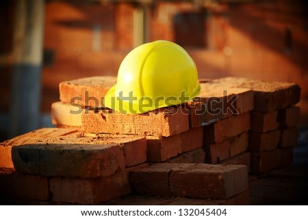 Under construction, helmet and bricks for building site - stock photo