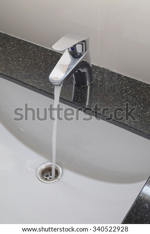 Under counter wash basin with modern style faucet - stock photo