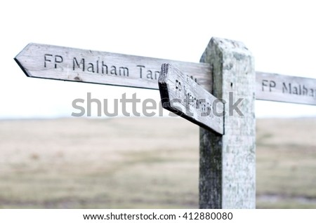 Under exposed image of wooden sign on the Yorkshire Dales, pointing to Malham land marks, cold and desolate  - stock photo