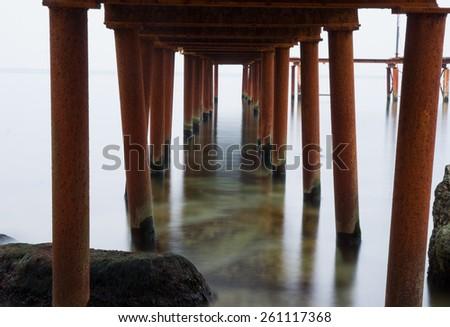 under pier pylons in water - stock photo