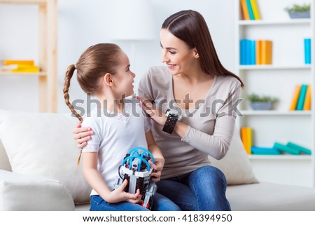 Under protection of mother.  Pleasant beautiful woman sitting on the couch with her daughter and talking while playing with robot  - stock photo