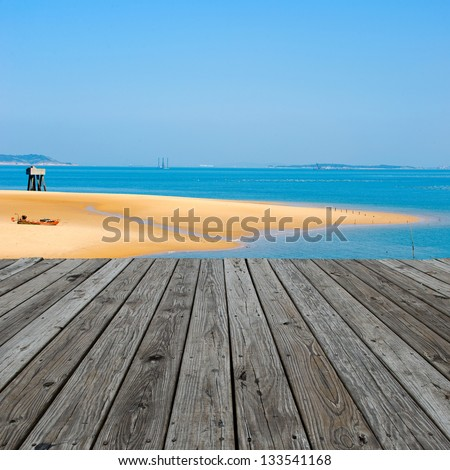 Under the blue sky, wood platform beside the sea. - stock photo