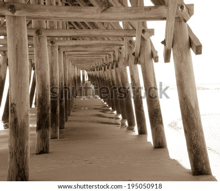 Under The Boardwalk. Underside of pier jutting into the Atlantic Ocean.  Myrtle Beach, South Carolina.   - stock photo