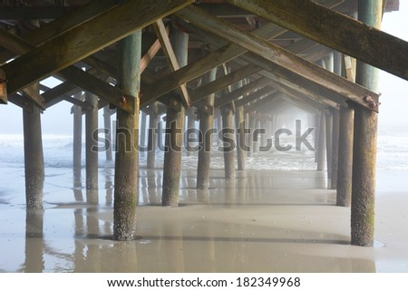 Under the pier on a foggy day - stock photo