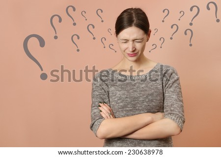 Under the pressure, Portrait of young woman with distressed facial expression and a lot questions marks around - stock photo