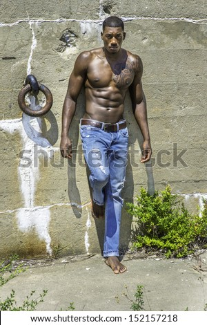 Under the sunshine, a masculine black guy, wearing blue jeans, barefoot and half naked, is standing by a wall, confidently looking forward. / Portrait of  Young Black Fitness Guy  - stock photo