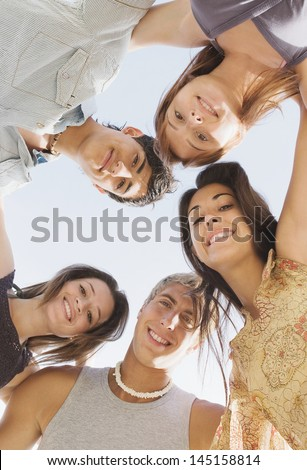 Under view of a group of five teenagers friends looking down at the camera and smiling with their arms around each others shoulders against a sunny sky while on vacation during the summer break. - stock photo
