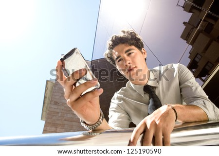 Under view of a young aspirational businessman using a smart phone while leaning on a banister outside a modern glass office building in the city. - stock photo