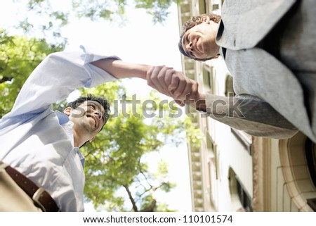 Under view of two businessmen shaking hands in the financial district of the city, smiling. - stock photo
