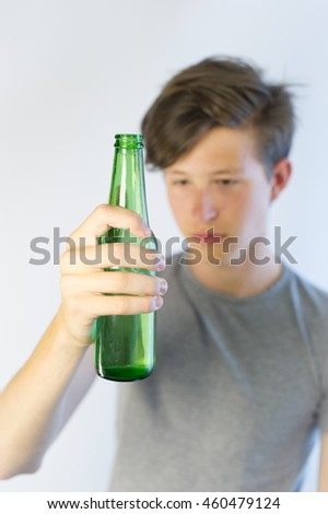 Underage alcohol drinker looking at a beer bottle.