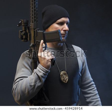 Undercover Law Enforcement Special Agent with rifle, looking angry off camera on dark background. - stock photo