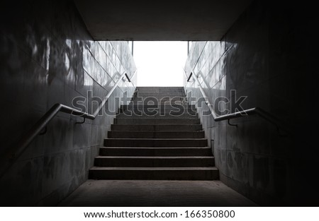Underground passage with stairs in the glowing end - stock photo