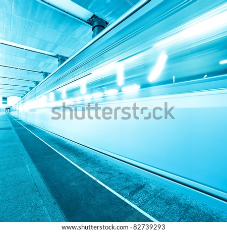 underground platform with moving train - stock photo