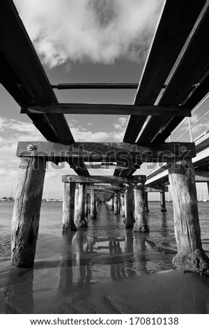 Underneath a crumbling, old pier on a calm day in black and white. - stock photo