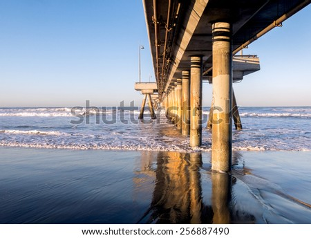 Underneath a pier with thick, wooden pillars, the ocean up front and a blue morning sky above.