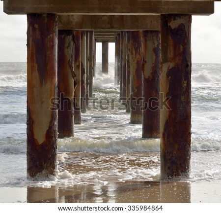 Underneath ocean fishing pier - stock photo