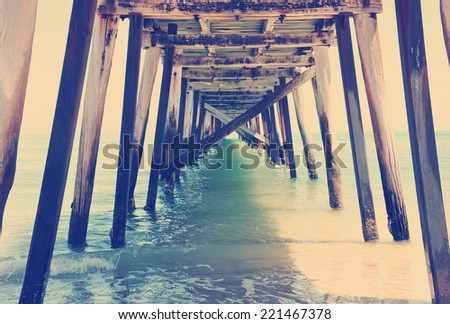 Underneath the Grange Jetty pier with retro vintage style filter. - stock photo