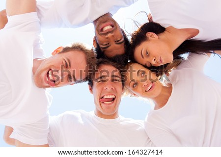 underneath view of friends with funny faces outdoors - stock photo