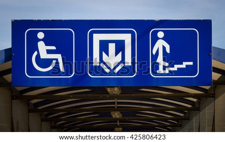 Underpass with three white symbols on a blue background - invalids - disables, exit and subway.