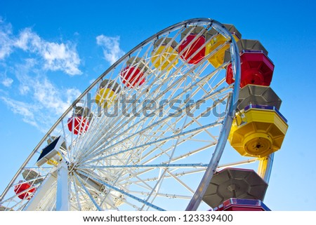 Underside view of a ferris wheel rotating downward on California's Santa Monica Pier. - stock photo