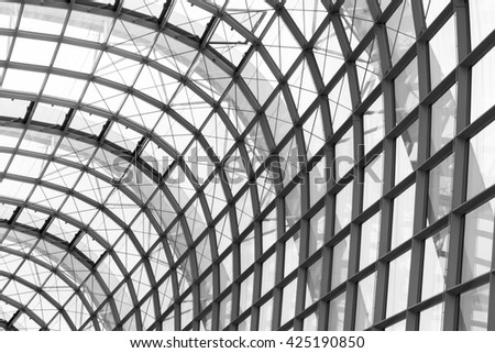 underside wide angled and perspective view to steel blue glass airport ceiling through high rise building skyscrapers, business concept of successful industrial architecture,black and white photo - stock photo