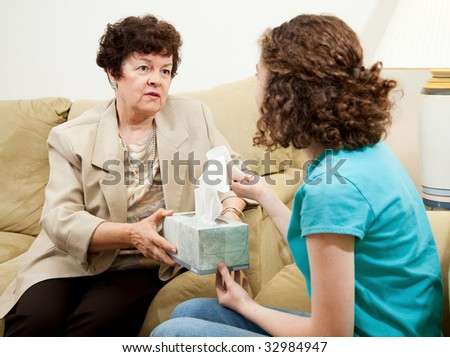 Understanding therapist handing tissue box to an upset teen patient.